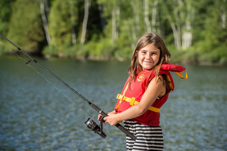 Jeune fille qui pêche sur un quai