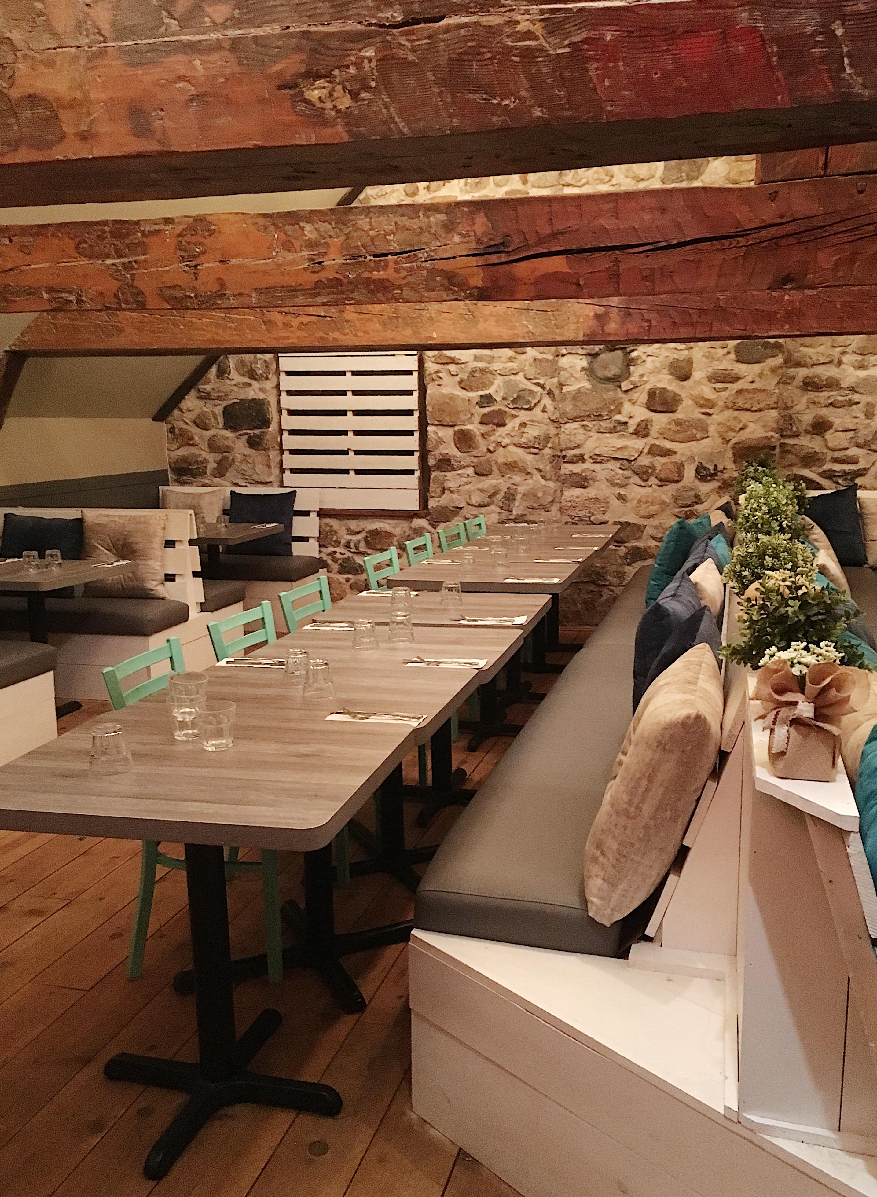 Salle privée du restaurant le Vice-Caché avec poutre en bois et mur de pierre