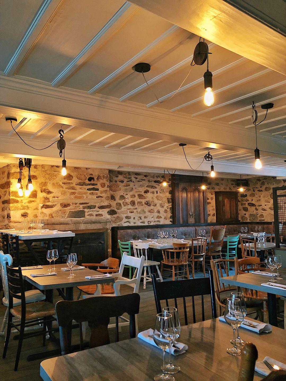 Intérieur du restaurant Vice-Caché avec ses chaises à l'ancienne et son mur de pierre